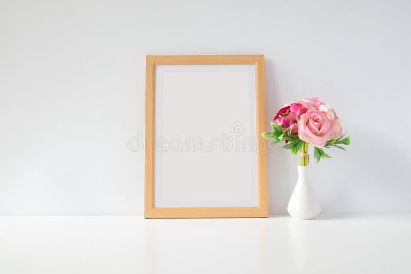 Imite encima de marco de la foto con las flores en la tabla imagen de archivo