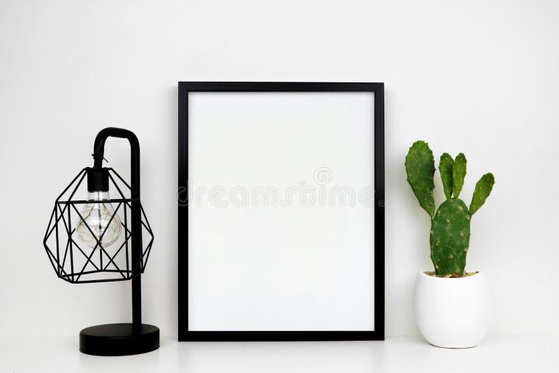 Imite encima de marco negro, de la planta del cactus y de la lámpara industrial del estilo en un estante blanco o del escritorio  imagen de archivo libre de regalías