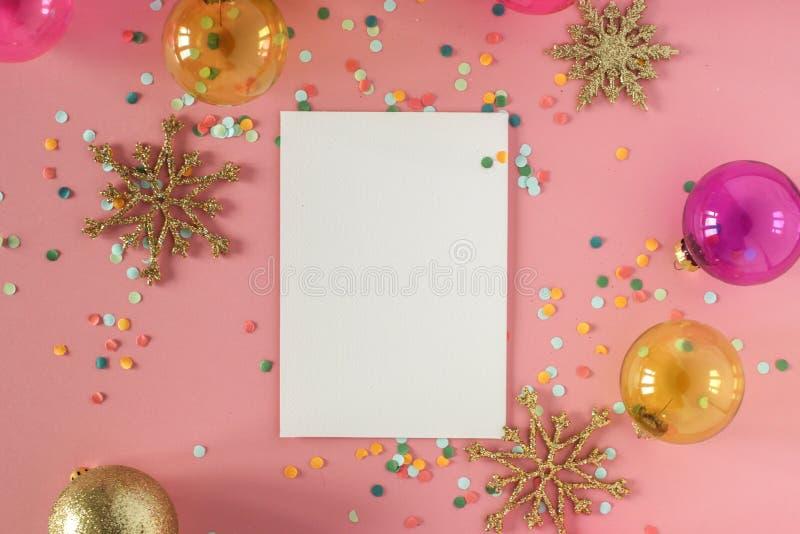Imite encima de tarjeta en un fondo rosado con sus decoraciones y confeti de la Navidad Invitación, tarjeta, papel Lugar para el  foto de archivo libre de regalías