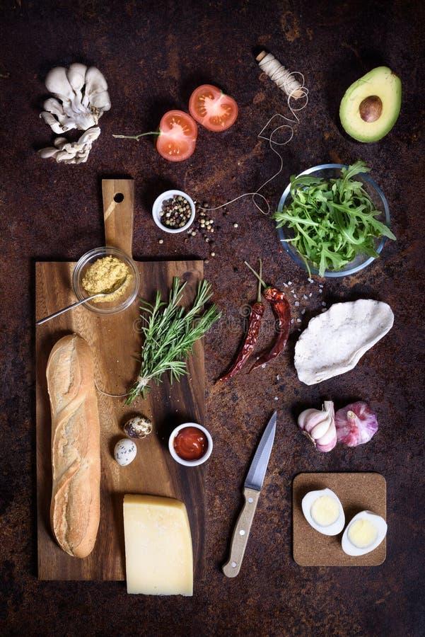 Imite encima del bocadillo y los ingredientes el cocinar fijados en fondo marrón rústico Copie el espacio para el texto, endecha  imagen de archivo
