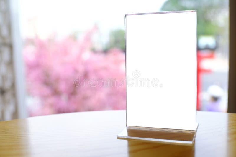 Imite encima del marco del menú que se coloca en el espacio de madera de la tabla para el texto Valent foto de archivo