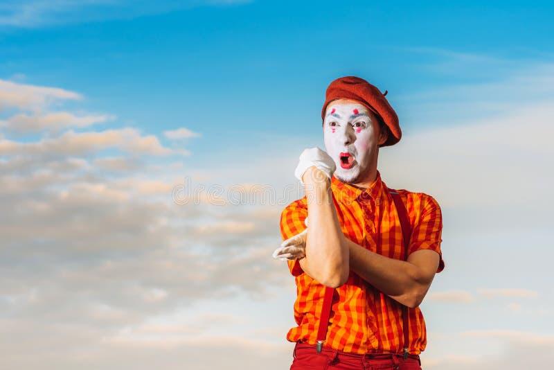 Imite la pantomima de las demostraciones contra el cielo azul fotografía de archivo