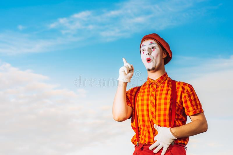 Imite la pantomima de las demostraciones contra el cielo azul foto de archivo