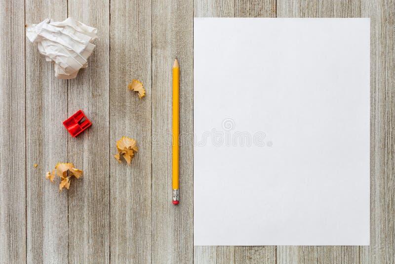 Imite para arriba con la hoja, el lápiz, las virutas y los sacapuntas del Libro Blanco en fondo de madera foto de archivo libre de regalías
