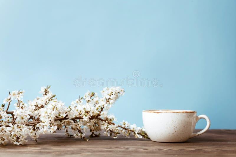 Imite para arriba con la rama de árbol y la taza de café florecientes en la tabla de madera con el fondo azul Ciérrese encima de  foto de archivo libre de regalías