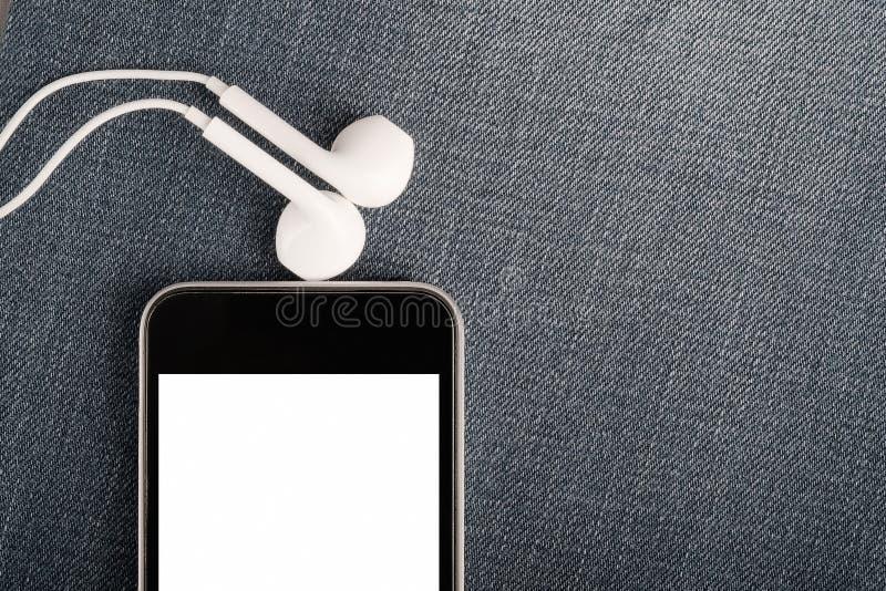 Imite para arriba con smartphone y los auriculares modernos en fondo del dril de algodón fotografía de archivo