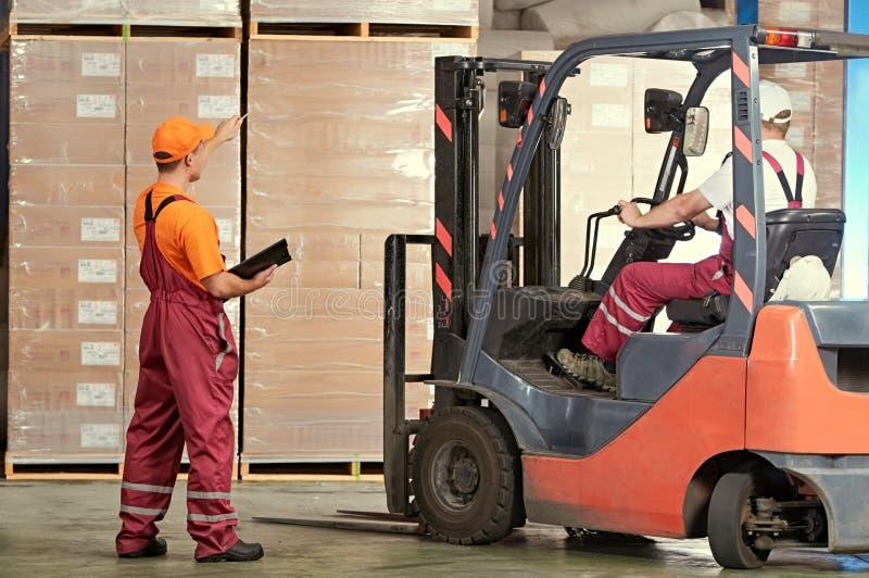 Immagazzinamento e stoccaggio i lavoratori del magazzino lavora con il caricatore del carrello elevatore fotografia stock