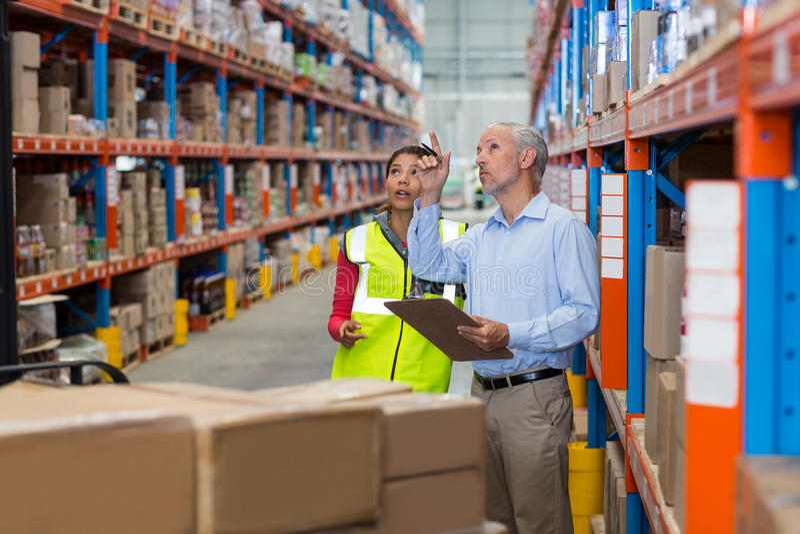 Immagazzini il responsabile e la lavoratrice che interagiscono mentre controllano l'inventario immagine stock libera da diritti