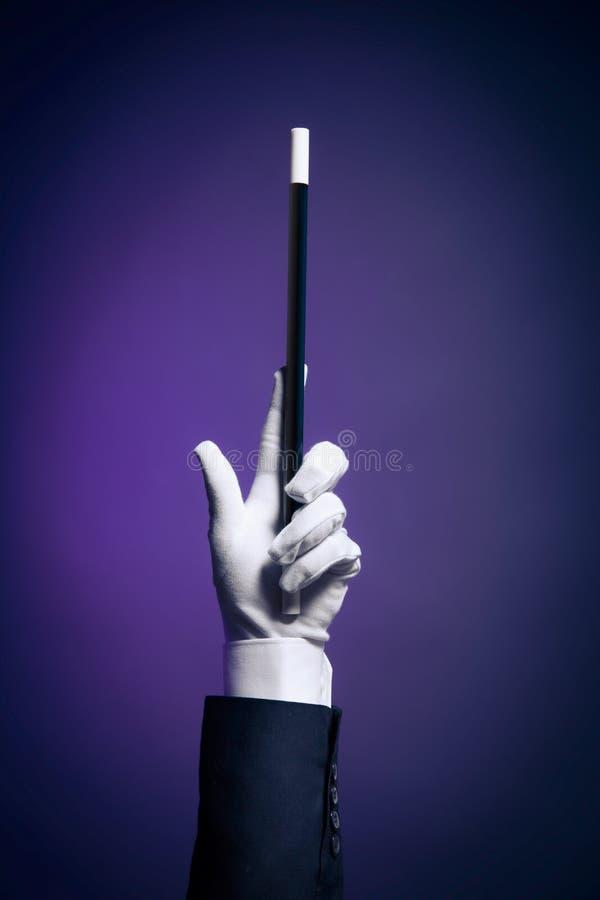 Immagine ad alto contrasto della mano del mago con la bacchetta magica fotografia stock