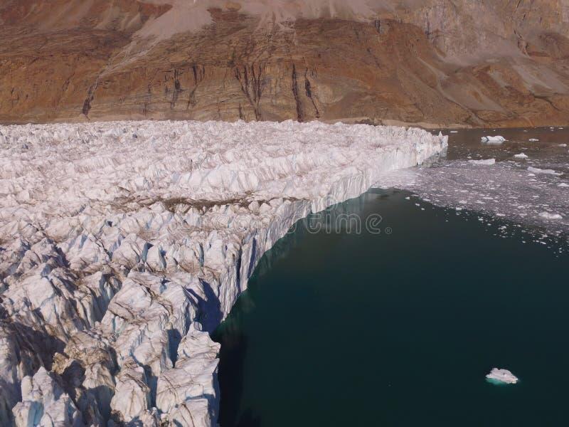 Immagine aerea del fuco obliquo dell'estremità di un ghiacciaio in un fiordo in Groenlandia di nordest fotografie stock libere da diritti