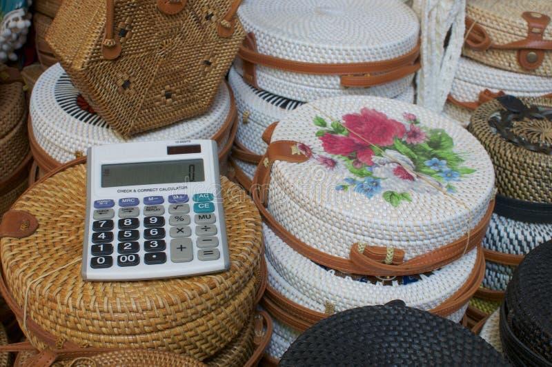 Immagine alta vicina di un calcolatore con le borse del rattan nei precedenti a Ubud Art Market, Bali immagine stock libera da diritti