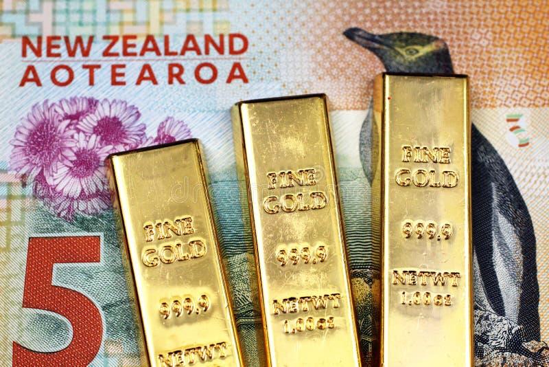 Immagine alta vicina di una banconota da cinque dollari della Nuova Zelanda con tre piccoli lingotti nella macro immagini stock