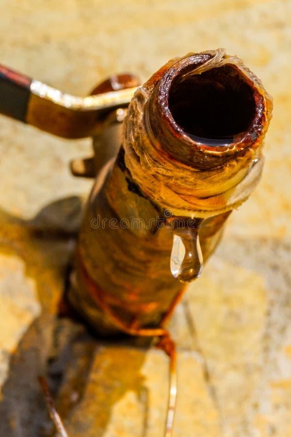 Immagine alta vicina di una goccia della sgocciolatura dell'acqua da un rubinetto arrugginito immagini stock libere da diritti