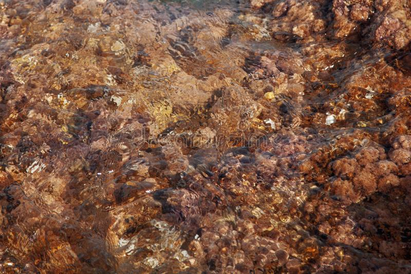 Immagine astratta del fondo di struttura della pietra del mare nei vawes di acqua fotografia stock