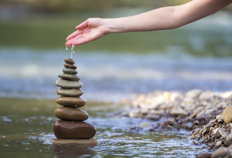 Immagine astratta del primo piano dell'acqua di versamento della mano della donna su nazionale ruvido immagine stock