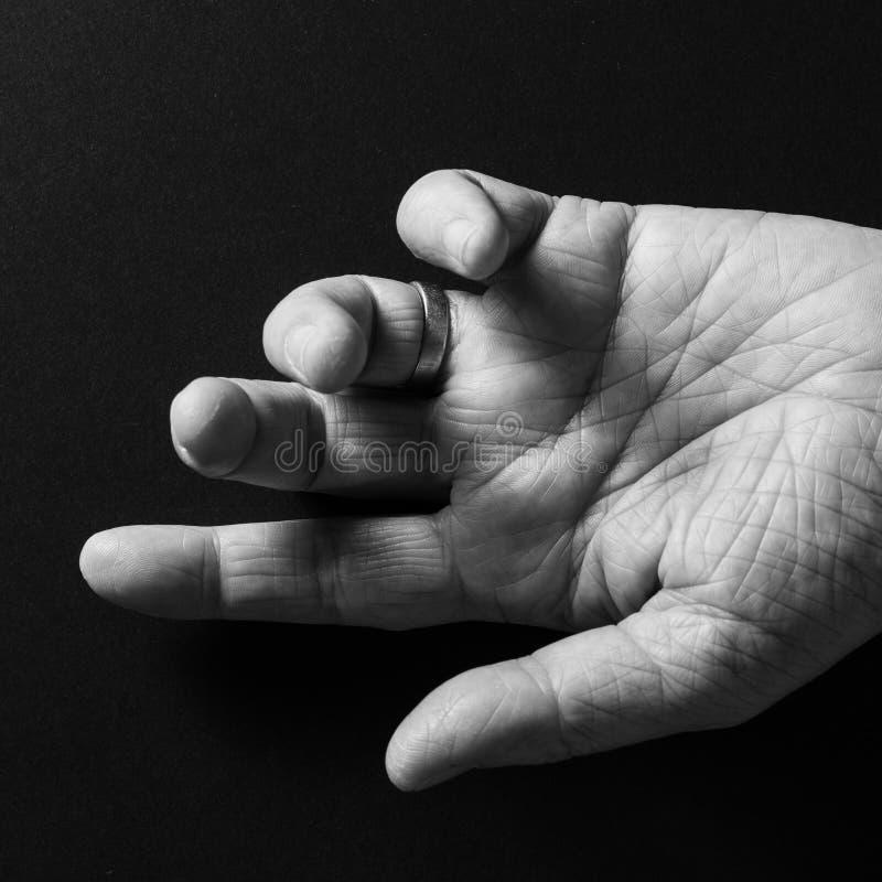 Immagine bianca e nera della mano dell'uomo, palma aperta su ed indicando, isolato contro un fondo nero con la luce radente dramm fotografia stock