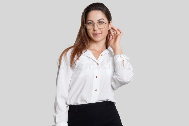 Immagine in bianco e nero dei vestiti vestiti progettista femminile sembranti piacevoli, grandi vetri rotondi, pronti a presentar immagine stock libera da diritti