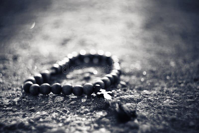 Immagine in bianco e nero del rosario di legno con un incrocio immagine stock