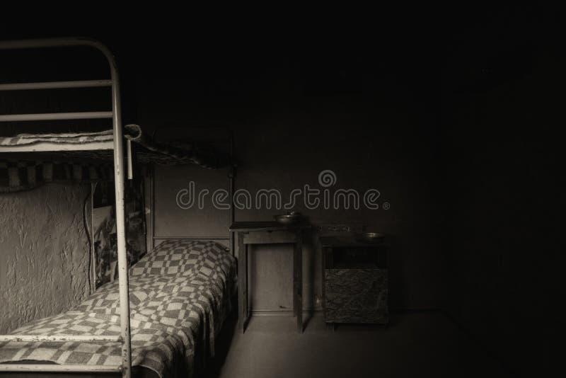 Immagine in bianco e nero della cella di prigione vuota scura con la cuccetta del ferro immagine stock