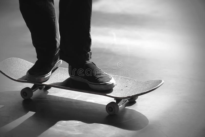 Immagine in bianco e nero delle gambe di una guida dell'uomo sul suo pattino immagini stock libere da diritti