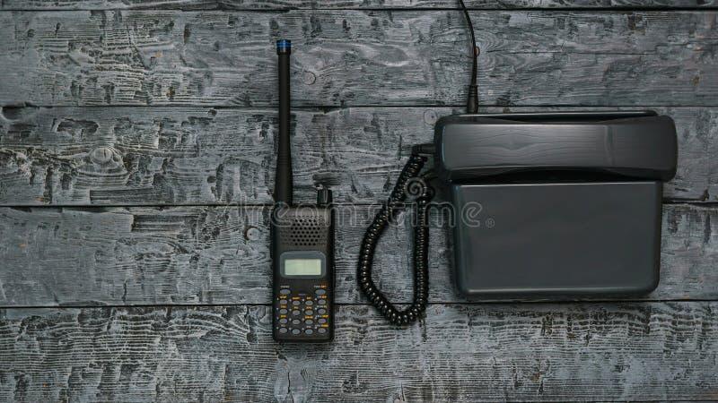 Immagine in bianco e nero di un walkie-talkie e di un telefono su una tavola di legno immagine stock libera da diritti