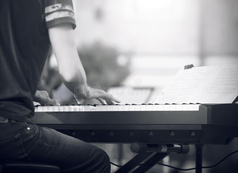 Immagine in bianco e nero, dove un pianista gioca una melodia sul sintetizzatore immagine stock libera da diritti