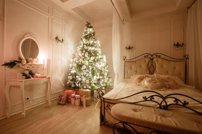 Immagine calma dell'albero classico interno del nuovo anno decorato in una stanza con il letto fotografie stock