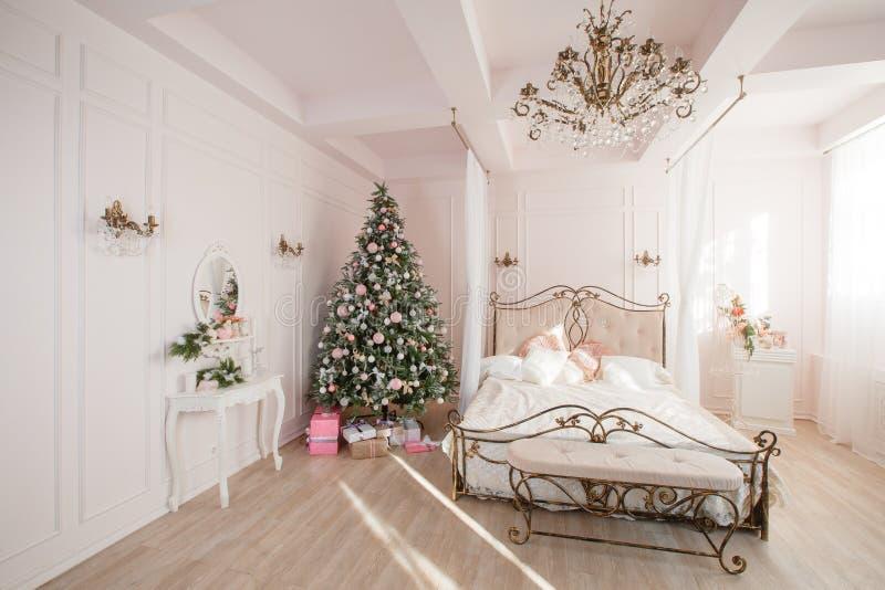 Immagine calma dell'albero classico interno del nuovo anno decorato in una stanza con il letto fotografie stock libere da diritti