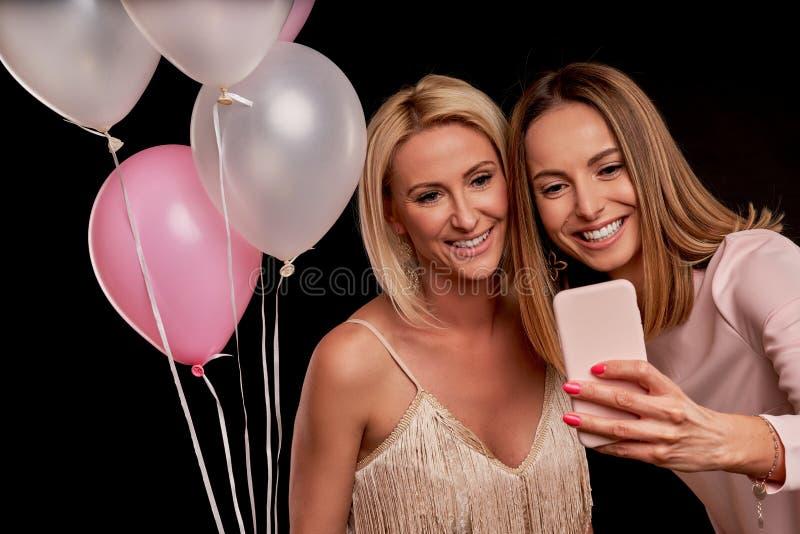 Immagine che presenta gruppo felice di amici che per mezzo dello smartphone fotografia stock
