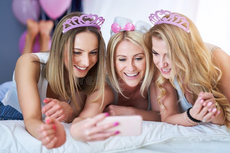 Immagine che presenta gruppo felice di amici che per mezzo dello smartphone immagine stock libera da diritti