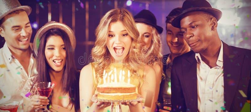 Immagine composita degli amici felici che celebrano compleanno con il dolce fotografie stock