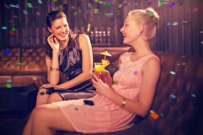 Immagine composita degli amici femminili che interagiscono a vicenda mentre avendo cocktail immagine stock