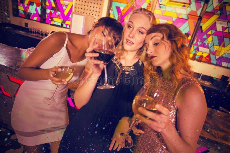 Immagine composita degli amici femminili che mangiano vetro di champagne e di vino fotografie stock
