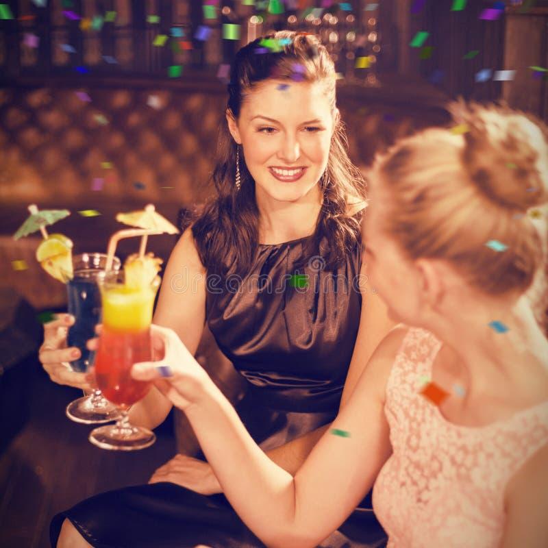 Immagine composita degli amici femminili che tostano i vetri del cocktail fotografia stock libera da diritti
