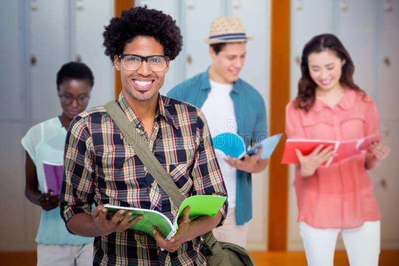 Immagine composita degli studenti alla moda che sorridono insieme alla macchina fotografica immagine stock libera da diritti