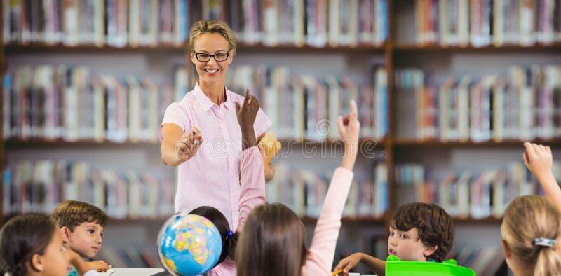 Immagine composita degli studenti che sollevano le mani mentre insegnamento dell'insegnante fotografia stock