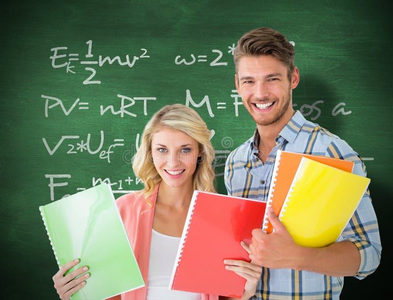 Immagine composita degli studenti felici che sorridono alla macchina fotografica fotografie stock libere da diritti