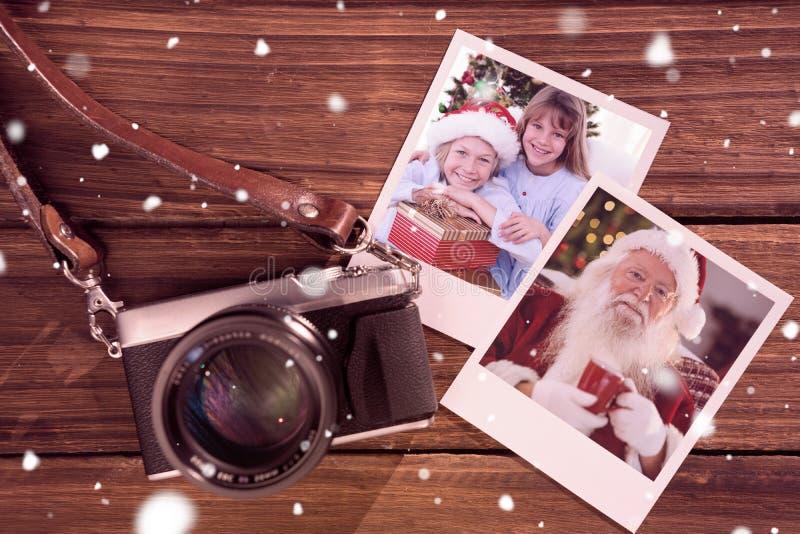 Immagine composita dei fratelli germani sorridenti che tengono i regali di natale fotografia stock