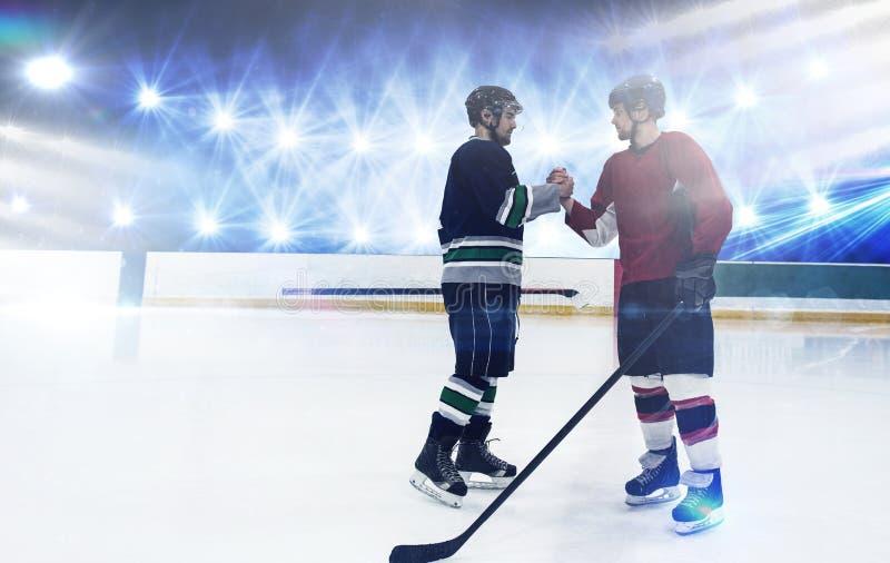 Immagine composita dei giocatori di hockey su ghiaccio che stringono le mani alla pista di pattinaggio immagini stock