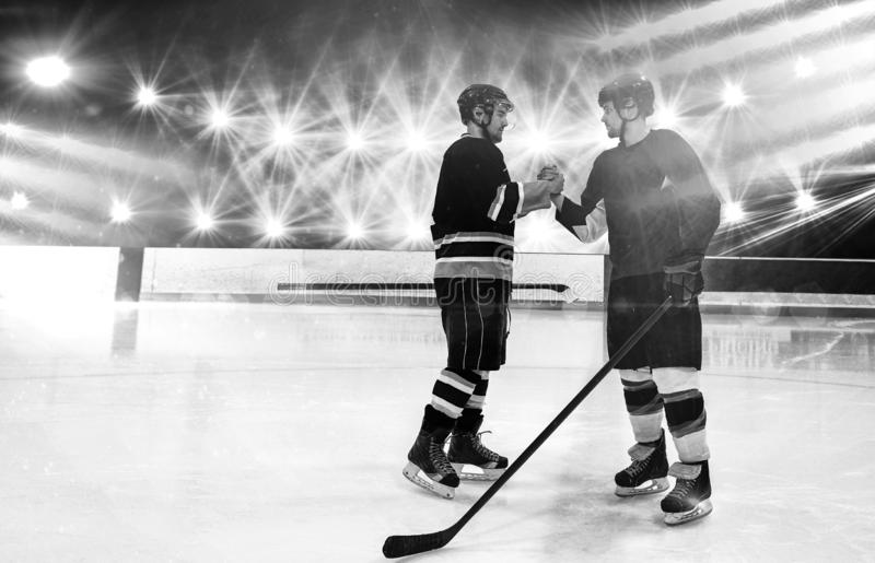 Immagine composita dei giocatori di hockey su ghiaccio che stringono le mani alla pista di pattinaggio immagine stock libera da diritti
