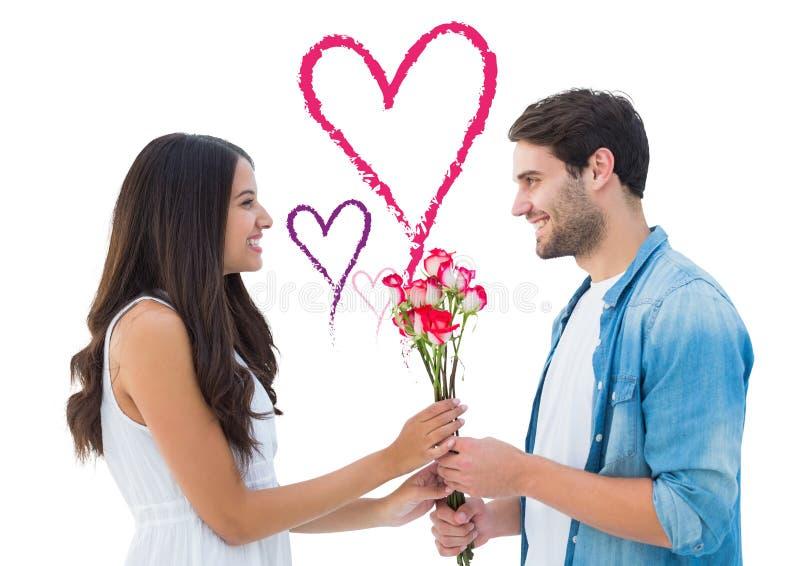 Immagine composita dei pantaloni a vita bassa felici che dà alla sua amica le rose fotografia stock