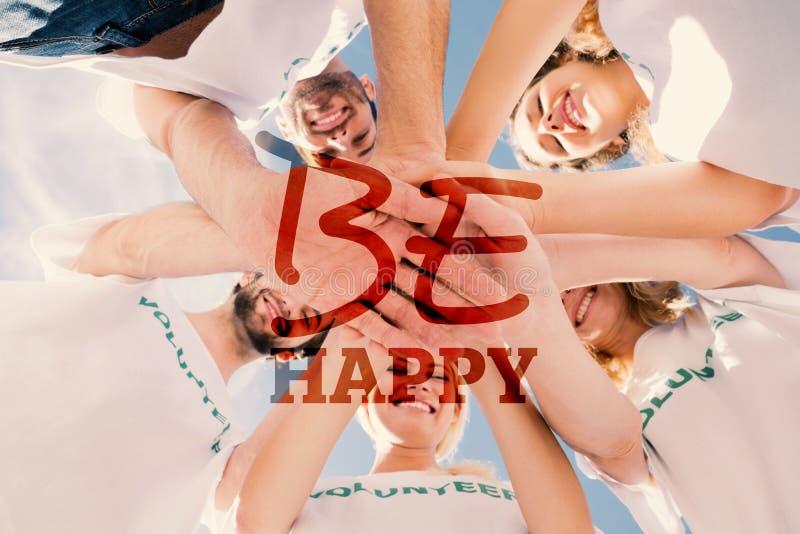 Immagine composita dei volontari felici con le mani insieme contro cielo blu fotografie stock