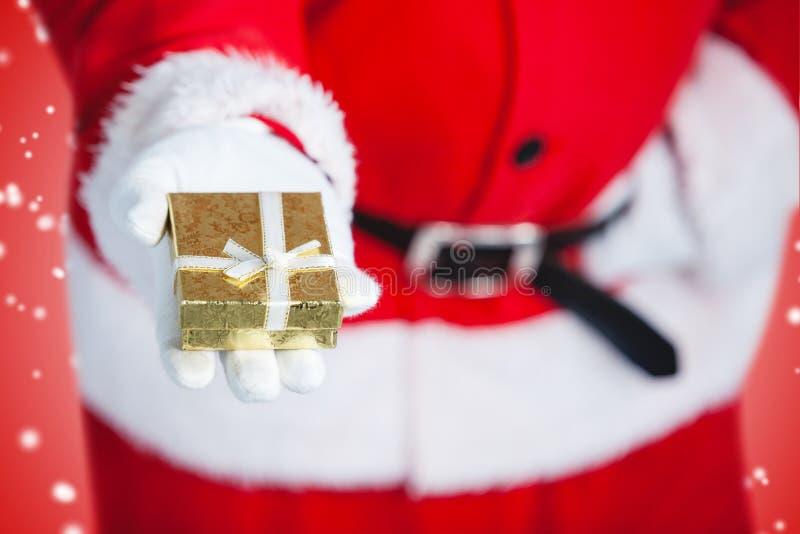 Immagine composita del Babbo Natale che giudica un contenitore di regalo disponibile fotografie stock
