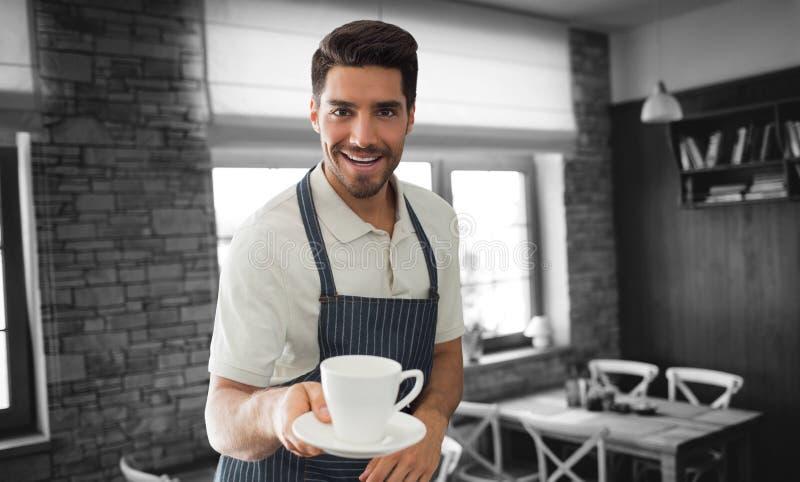 Immagine composita del cameriere che indica una tazza di caffè immagine stock