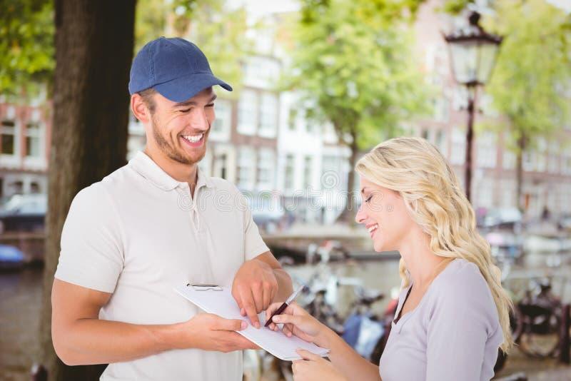 Immagine composita del fattorino felice che ottiene firma dal cliente immagini stock libere da diritti