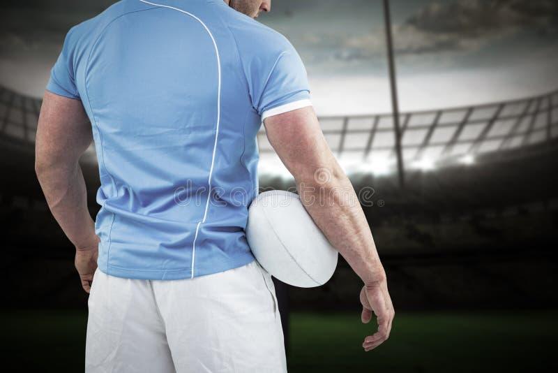 Immagine composita del giocatore di rugby che sta con la palla immagini stock