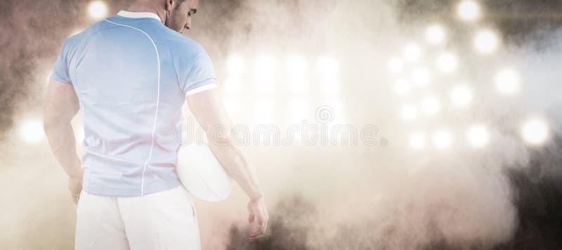 Immagine composita del giocatore di rugby che sta con la palla fotografia stock