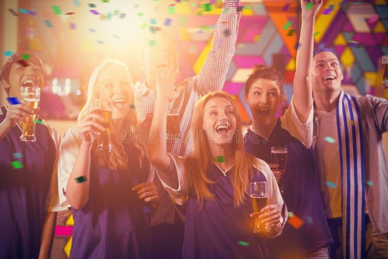 Immagine composita del gruppo di amici che incoraggiano nel partito mentre mangiando vetro di champagne fotografia stock