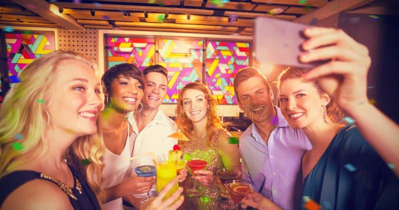 Immagine composita del gruppo di amici che prendono selfie dal telefono cellulare mentre avendo cocktail fotografia stock libera da diritti