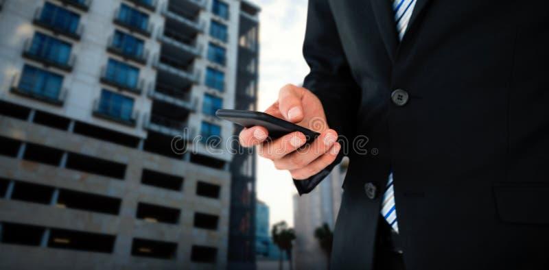 Immagine composita del midsection di invio di messaggi di testo dell'uomo d'affari sul telefono cellulare immagini stock